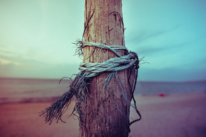 close up of pole in the beach with rope twisted on it, moved by wind - loneliness, isolation concept