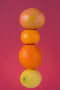 Close up of ripe fresh citrus fruits, tangerine fruit, orange, lemon, grapefruit isolated on pink background