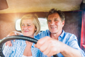 Close up of senior couple inside a pickup truck, hugging, man holding a steering wheel