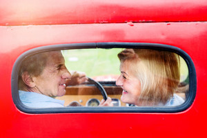 Close up of senior couple inside a pickup truck, man holding a steering wheel, rear view