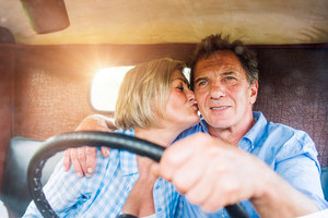Close up of senior couple inside a pickup truck, man holding a steering wheel, woman kissing him