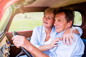 Close up of senior couple inside a red pickup truck, hugging, man holding a steering wheel