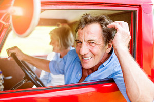 Close up of senior couple inside a red pickup truck, man holding a steering wheel, doing his hair