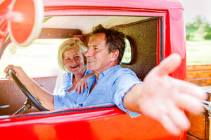 Close up of senior couple inside a red pickup truck, man holding a steering wheel, stretching out his arm