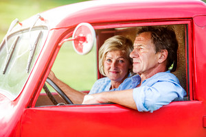 Close up of senior couple inside a red pickup truck, man holding a steering wheel