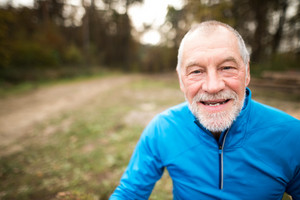Close up of senior runner in nature. Man in blue sweatshirt, resting, smiling.