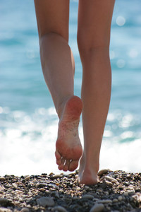 Close-up of slim legs of female walking down pebbles over blue sparkling background