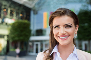 Close up of smiling elegant businesswoman in pink jacket and white shirt against glassy modern office building