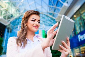 Close up of smiling elegant businesswoman in pink jacket and white shirt working on tablet against glassy modern office building