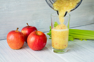 Close-up of Smoothies from apples and celery is poured into a glass from a food processor. Concept of healthy nutrition.