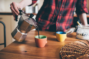 Close up of the hand of young woman pouring coffee from a moka in a cup - morning, breakfast, break concept