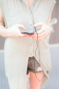 Close up of the hands of a young handsome caucasian blonde italian designer using a smartphone with earphones - technology, social network, music concept - wearing shorts and azure dress