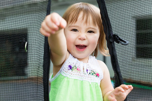 Close up of toddler girl playing on her trampoline