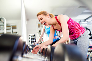 Close up of two attractive fit women in gym laughing, row of weights