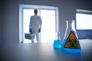 Close-up of two flasks with blue biohazard liquid with scientist on background
