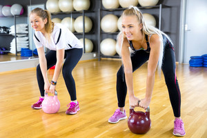 Close-up of two women training with kettlebells at gym