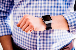 Close up of unrecognizable man in blue checked shirt using smart watch