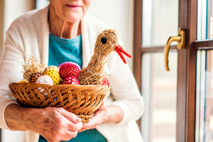 Close up of unrecognizable senior woman at the window in her house holding basket with Easter eggs and straw hen