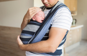 Close up of unrecognizable young father with his newborn baby son in sling at home