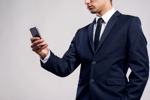 Close up of unrecognizable young hipster businessman with smartphone texting, reading, writing and searching something. Studio shot on gray background.