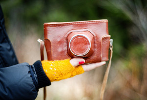 close-up of woman hand holding retro camera in brown leather case