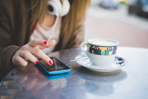 close up of woman hand using smartphone on a cafe bar table and cup of coffee