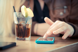 close up of woman hands using smart phones at the bar