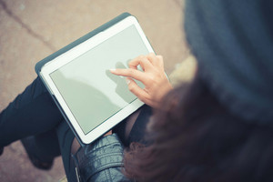 close up of woman hands using tablet outdoors