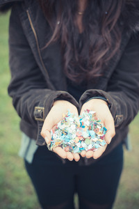 close up of woman hands with confetti outdoor