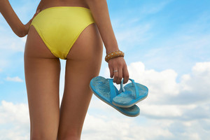 Close-up of woman holding a pair of flip flops