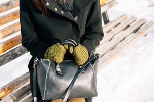 Close-up of woman in coat and gloves with a hand-bag sitting on a bench in winter