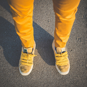 close up of yellow shoes legs of young beautiful hipster woman in the city