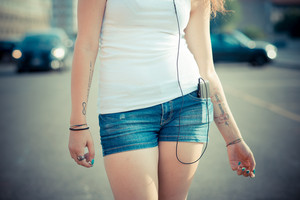 close up of young beautiful long curly hair hipster woman legs listening to music with smartphone in the city