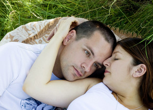 Close up of young couple lying on grass and hugging