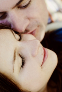 Close up of young couple lying on grass and kissing