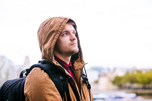 Close up of young hipster man in brown winter jacket, hood on head, in the streets of London