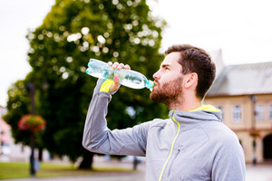 Close up of young hipster runner in town with water bottle, drinking