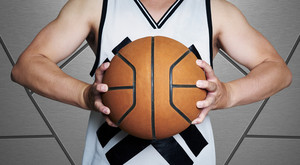 Close up of young man, midsection, holding a basketball