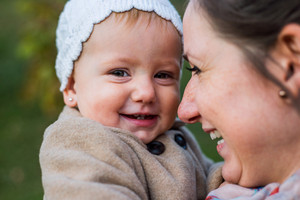 Close up of young mother holding her cute baby daughter, laughing. Winter. Outside.