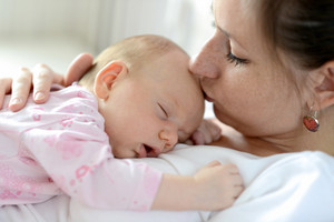 Close up of young mother holding her cute baby daughter lying on her, sleeping, kissing her