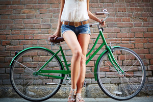 Close-up of young woman with bicycle standing against brick wall