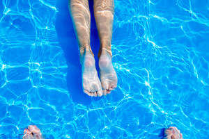 Close-up of young womans legs and mans toes in blue water in the swimming pool. Summer heat.