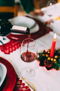 Close up on a bottle of red wine pouring a glass on a christmas table - christmas new year's eve, celebration concept