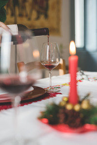 Close up on a hand pouring a glass with red wine on a table set for christmas - happy hour, beverage, relax concept