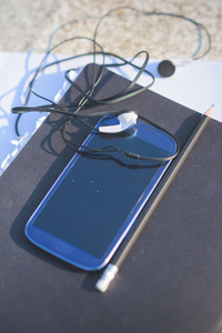 Close up on a smartphone, leaning on a sketchbook, with pencil and earphones beside it - technology, creativity, music concept