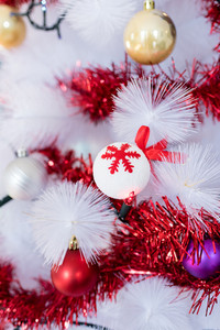 Close up on a tree decoration, a white ball with red snowflakes pictured on it - christmas, holiday, decoration concept