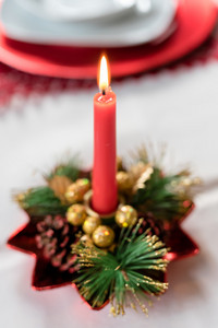 Close up on burning chrismas candle decoration - christmas, advent, celebration concept