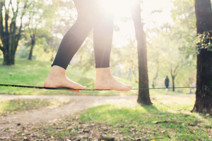 Close up on feet walking on tightrope or slackline outdoor in a city park in back light - slacklining, balance, training concept