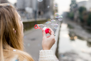 Close up on hand of young woman blowing and playing with bubble soap - childhood, happiness, serene concept