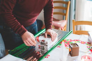 Close up on hands of young man wrapping christmas present - christmas, holiday concept
